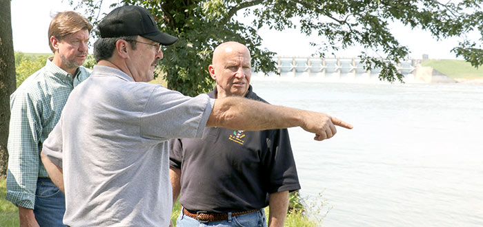 John Few, Sr., owner of Browder's Marina, points to the damage left by flooding at Livingston Dam Friday afternoon, while Rep. Kevin Brady and Judge Lovett look on.  (Photo by Megan Whitworth)