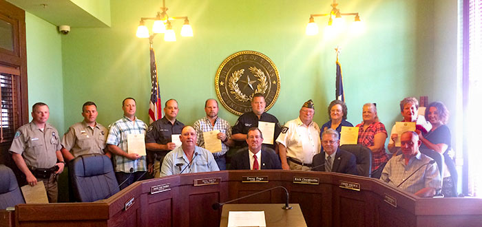 Standing (Left to Right)…Anthony King, Sam Shanafelt, Kevin Searcy, Sheriff Woody Wallace, Scott Womack, Deputy Chief Tommy Park, VFW Commander Don Chambers, Karlene Chambers, VFW Ladies Auxiliary President Delorise Grey, Sheran Casey and Jessica Dean.  Seated (Left to Right)…Precinct #3 Commissioner Neal Smith, County Judge Doug Page, Precinct #2 Commissioner Rich Chamberlin and Precinct #4 Commissioner Jimmy Brown.