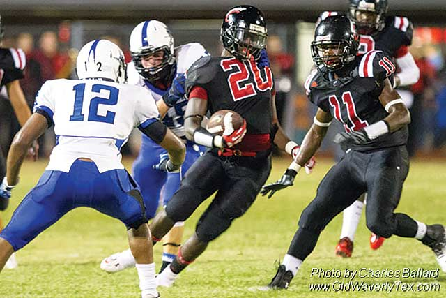 Edward Hayes (20) finds an opening in the tough Navasota Rattlers defensive line and makes a big gain following Jejuan McKibbins (11), for the Coldspring Trojans. Photo by Charles Ballard